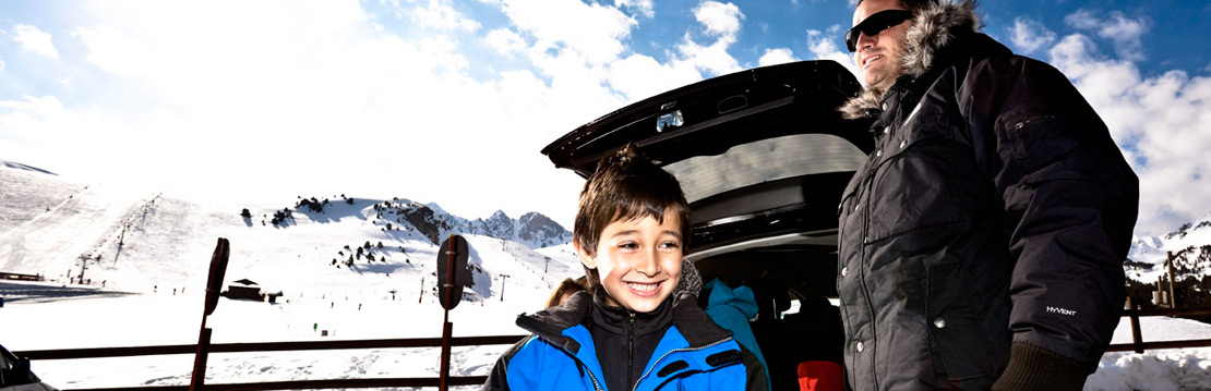 Excited child next to car and snowy mountains