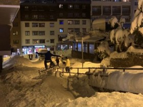 A snowboarder on a makeshift kicker on a side street